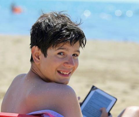 image of boy reading an ereader on the beach
