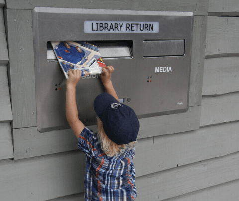 image of a child feeding a book into the book drop
