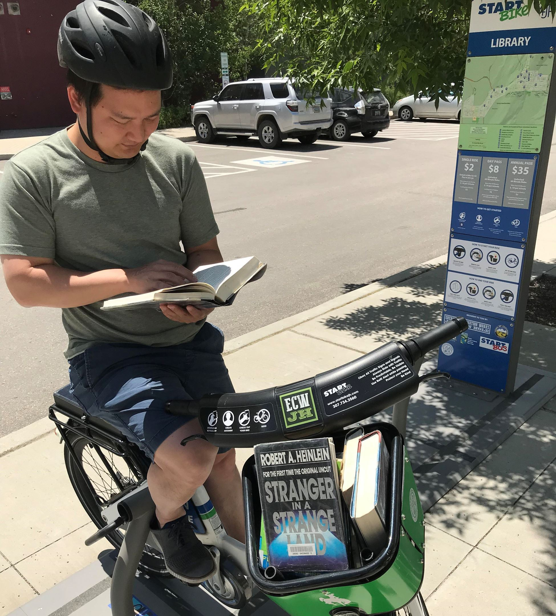 image of MIke Yin reading on a bicycle