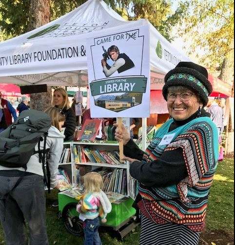 "image of volunteer holding a ""came for the library"" sign"